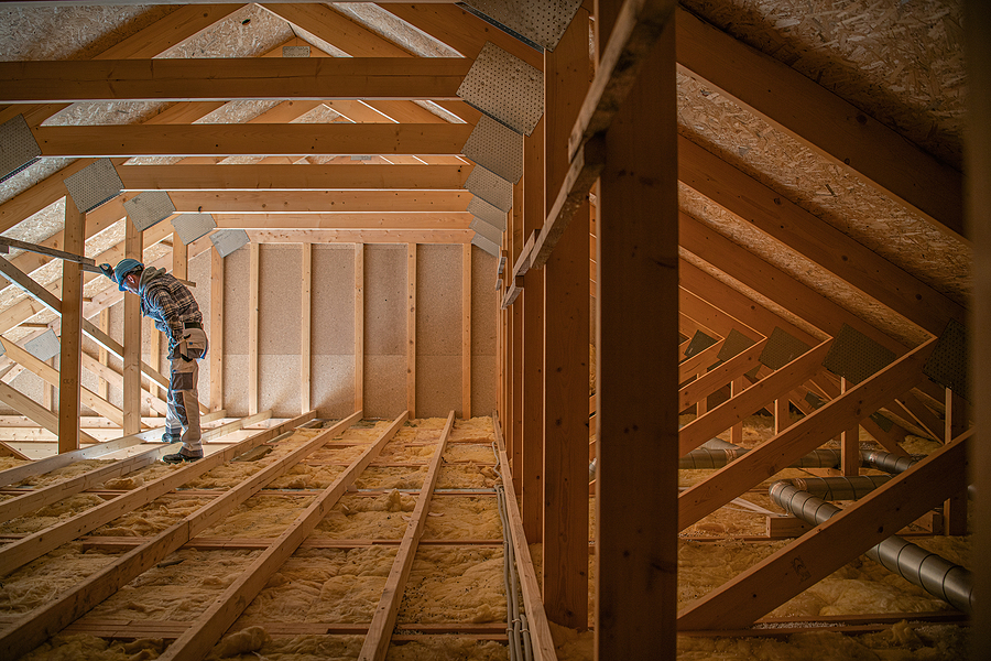 Construction Worker Looking Downstairs. Attic Wooden Roof Construction. House Cover. Wooden Structure.